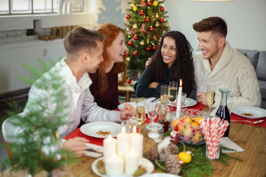 young adults sitting at a festive christmas table and laughing